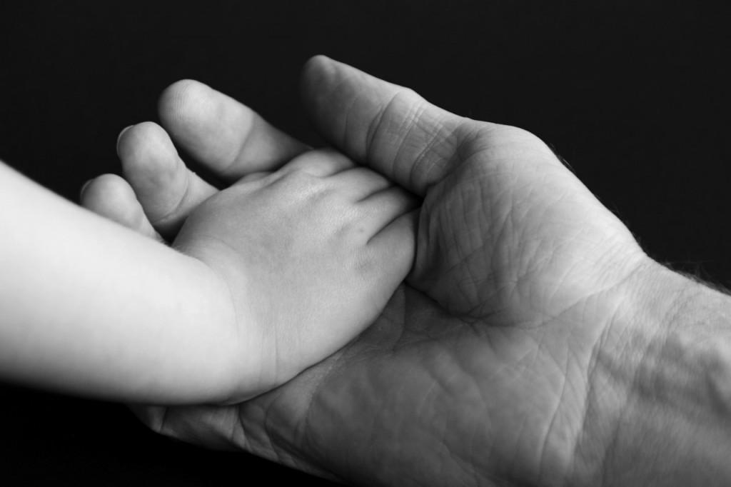 Hand eines Paten und Hand eines Patenkindes zeigen Vertrauen